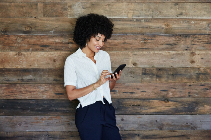 African American woman smiling standing against wood wall using her phone.